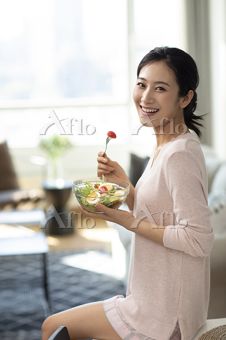 Happy young woman eating salad・・・