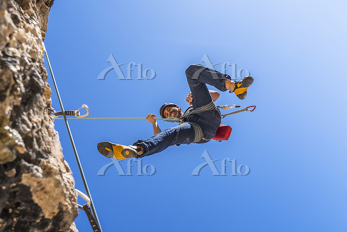 Smiling climber abseiling from・・・