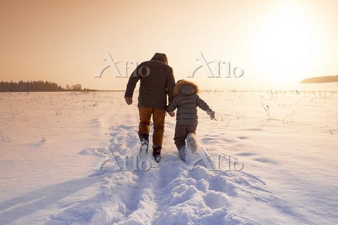 雪原を歩く親子の後ろ姿