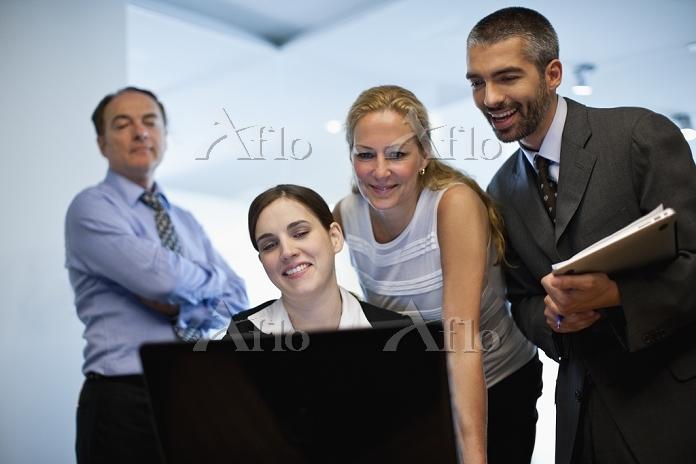 パソコンのモニタを囲む外国人ビジネスパーソン
