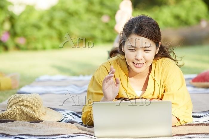芝生でパソコンを操作する日本人女性