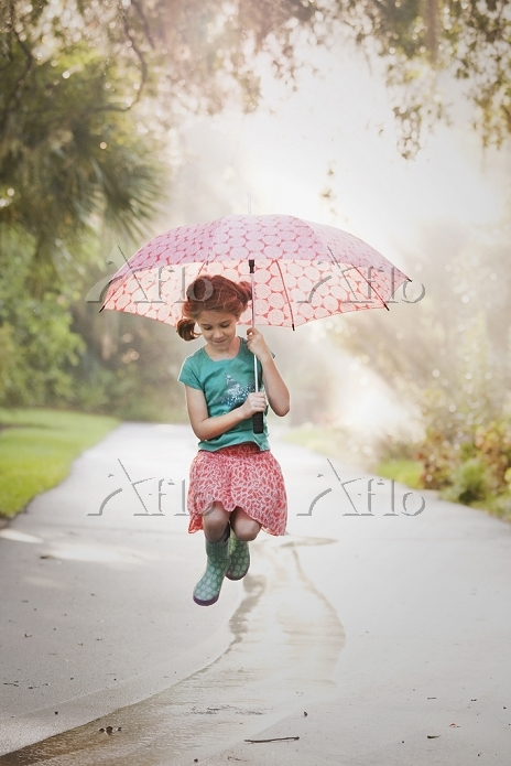 Girl holding up umbrella and j・・・