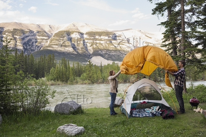 Couple assembling tent at camp・・・