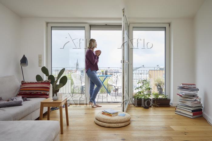 窓辺から遠くを見る外国人女性