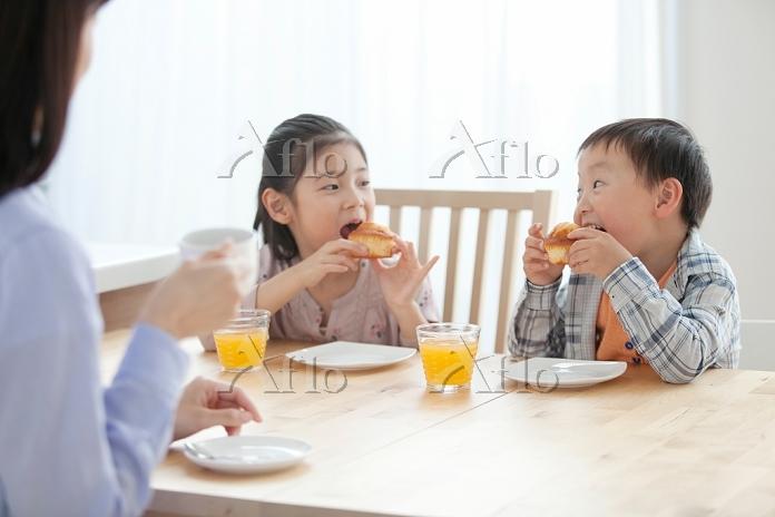 食卓に座る子供たちと母親