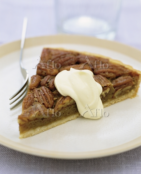 Slice of pecan pie with cream