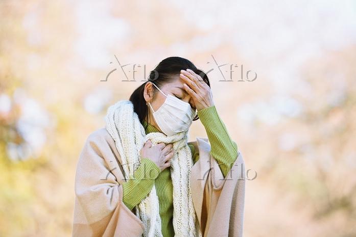 黄葉とマスクをしている日本人女性