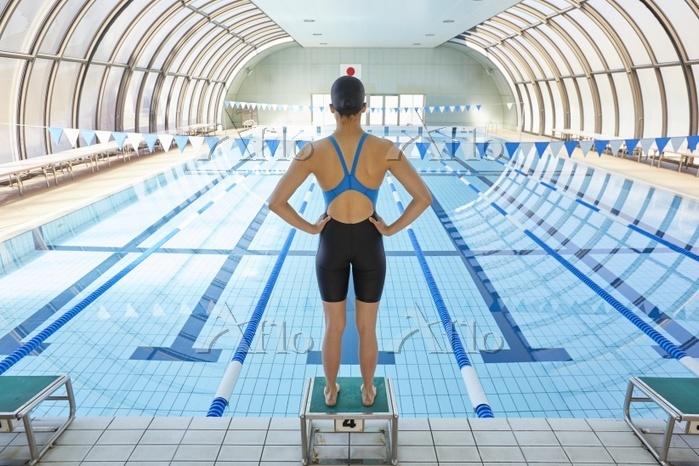 飛び込み台に立つ女子水泳選手
