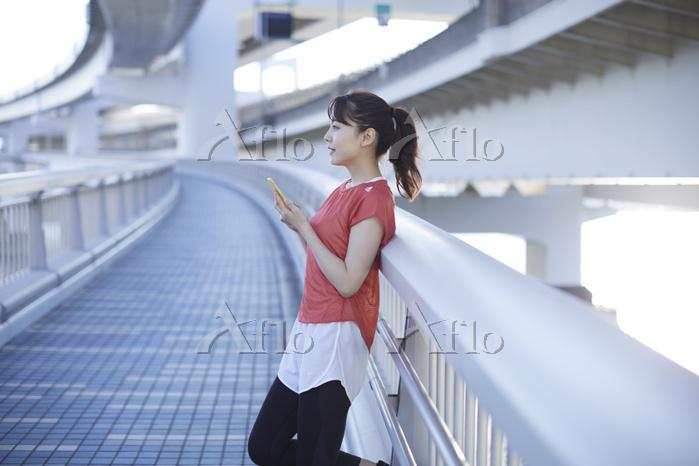 スマホを持つランニングウェア姿の女性