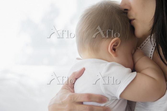 母親に抱かれて眠る外国人の赤ちゃん