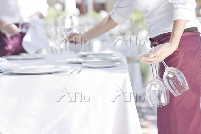 Waiter placing wine glasses on・・・