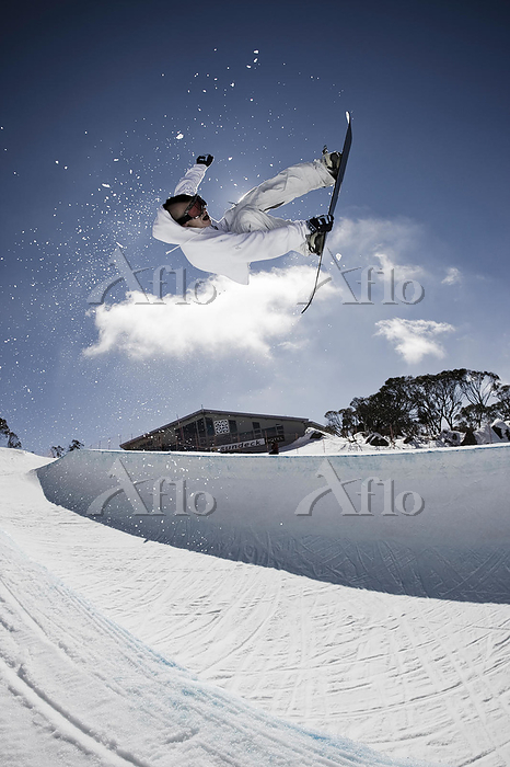 Snowboarder catching air in th・・・