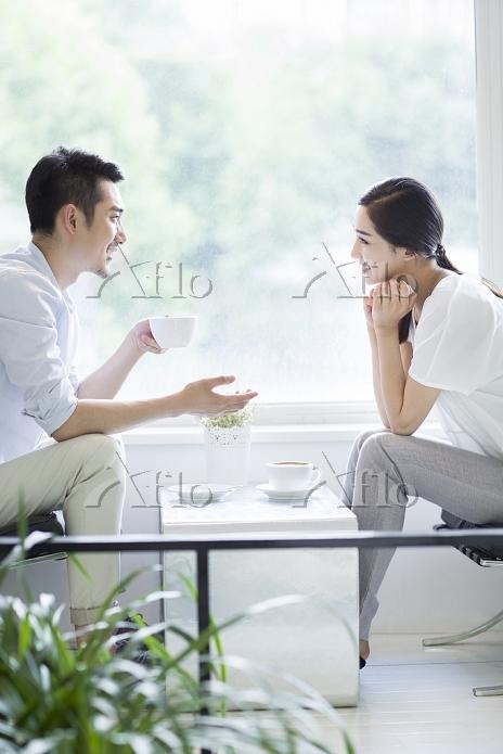 コーヒーを飲みながら話す男女