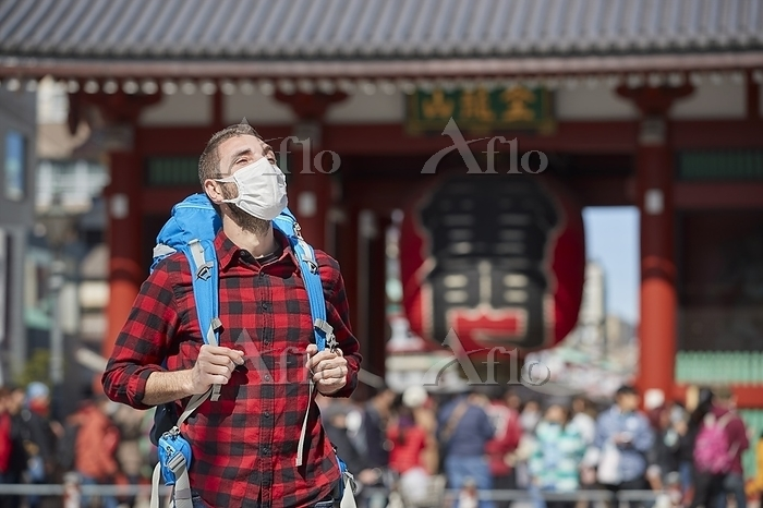 マスクをする外国人バックパッカー