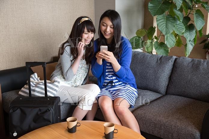 スマートフォンを一緒に見る若い日本人女性