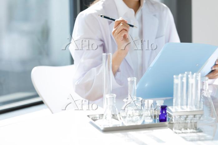 ペンを持つ白衣の研究員
