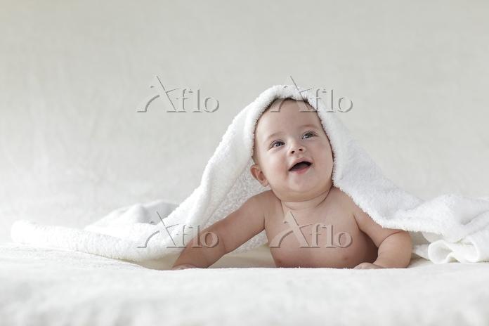 タオルをかぶった裸の赤ちゃん