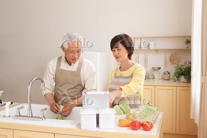 iPadを見て料理するシニア夫婦