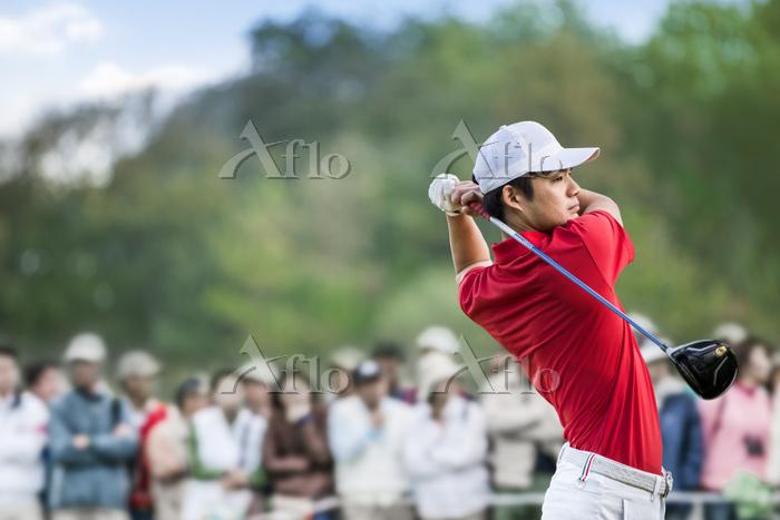 ティーショットを打つ男子ゴルフ選手