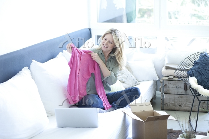 Woman sitting on couch unpacki・・・