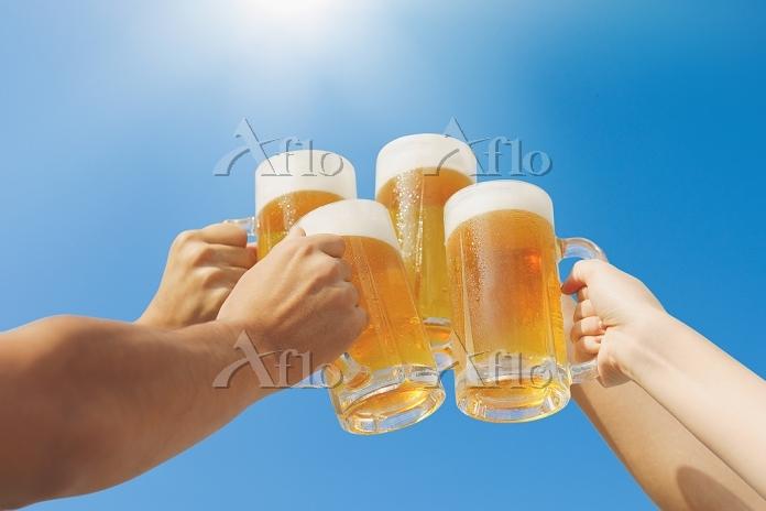 ビールで乾杯するグループと青空 夏の食