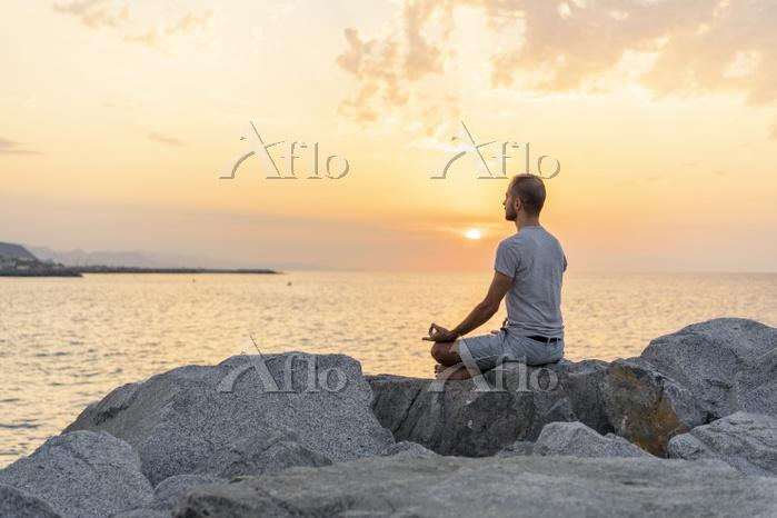 Spain. Man meditating during s・・・