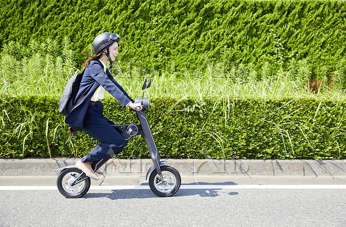 電動バイクで通勤するビジネスウーマン