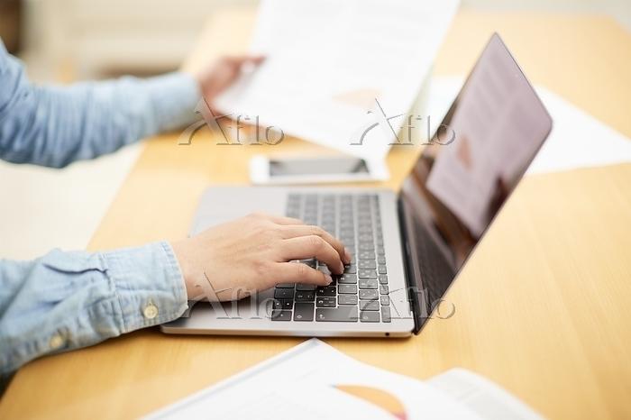 ノートパソコンを操作する手元