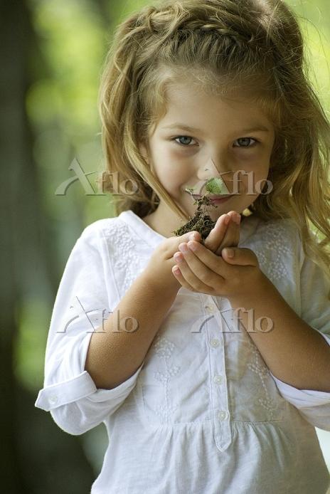 Girl holding seedling, portrai・・・