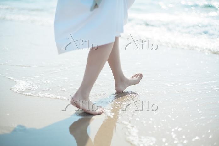 波打ち際を歩く女性の足