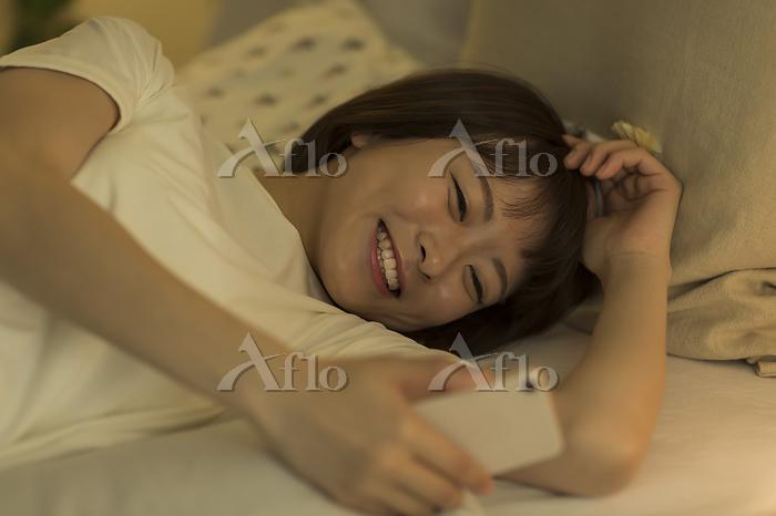 ベッドでスマホをみる日本人の若い女性