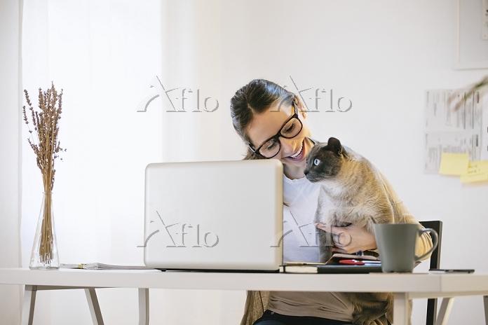 家でパソコンを使う外国人女性