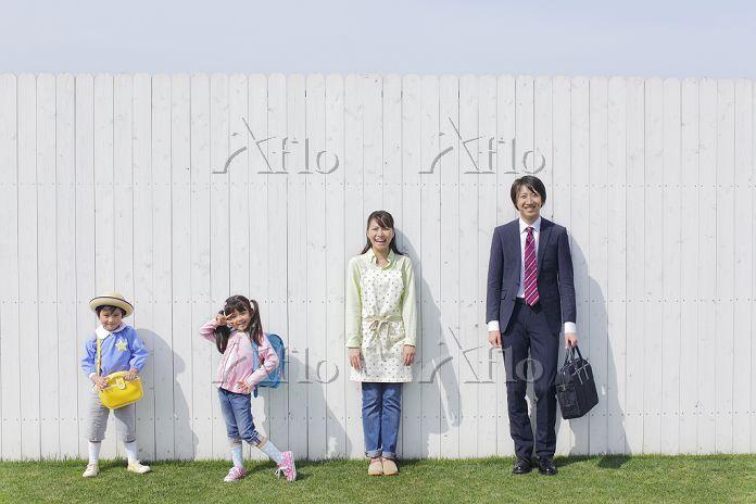 白い壁の前に並ぶ出勤と登校前の日本人家族