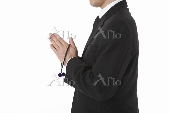 数珠を持ち合掌する喪服姿の日本人男性 横