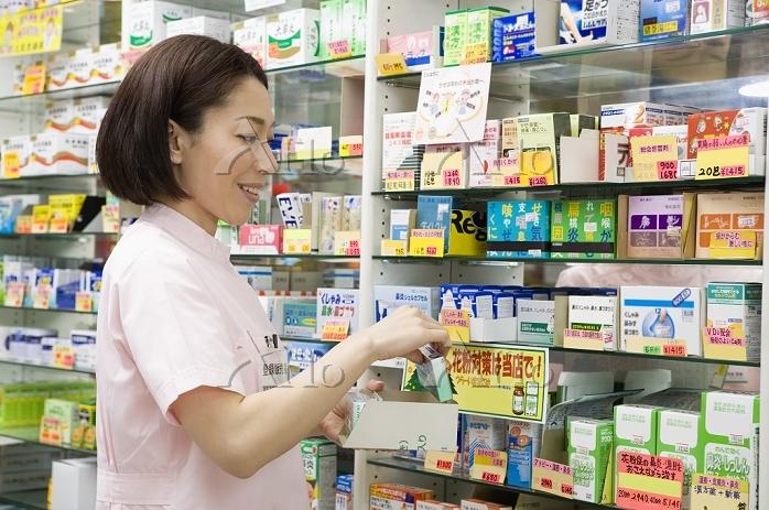 商品棚を整理する女性登録販売者