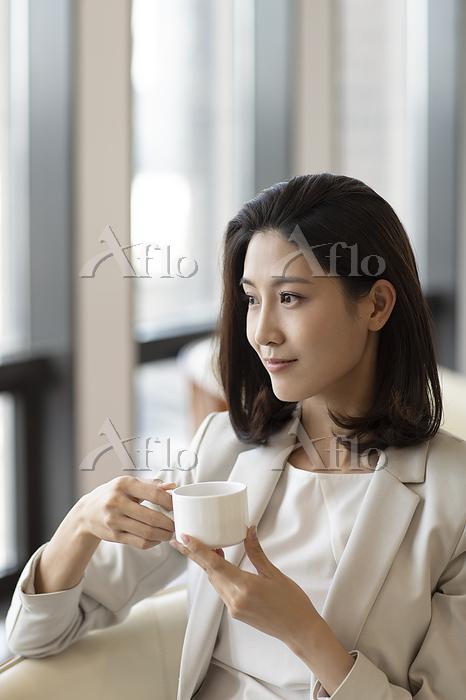 Confident businesswoman drinki・・・