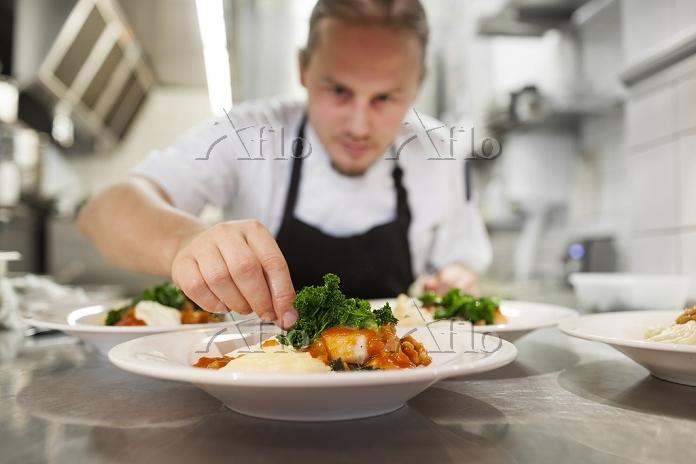 レストランで料理の盛り付けをするシェフ