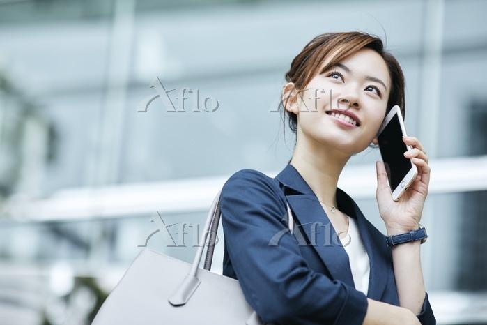 電話を掛ける日本人ビジネスウーマン