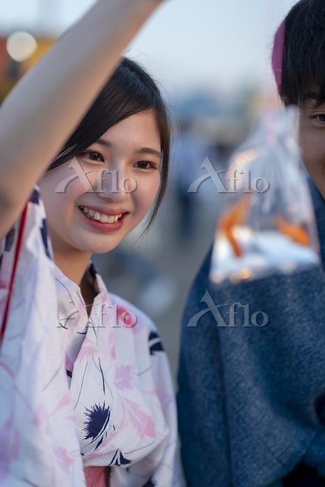 お祭りで金魚を見せる浴衣の日本人女性