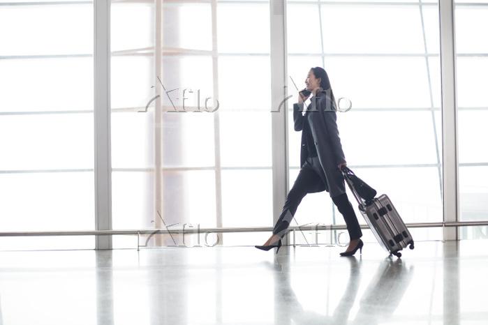 空港で電話をかけるビジネスウーマン