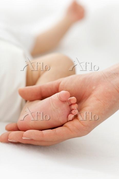 赤ちゃんの足と母親の手