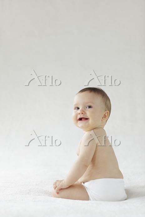 ベッドの上に座る裸の赤ちゃん