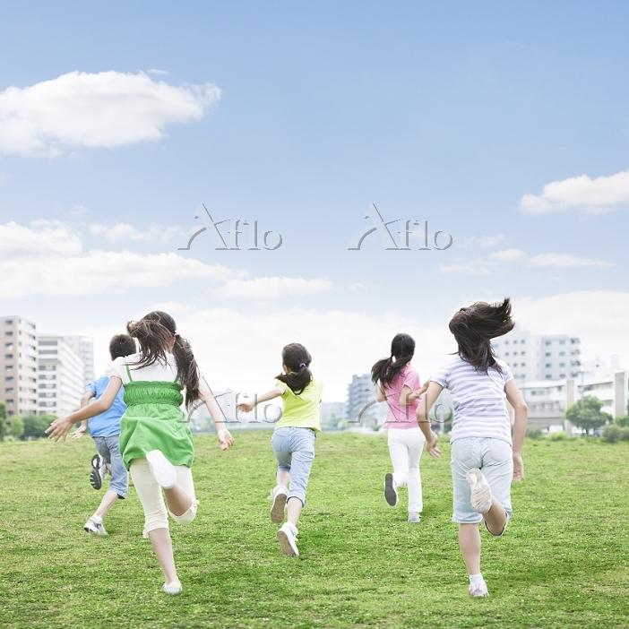 草原を走る子供達の後ろ姿