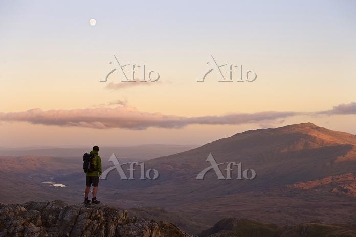 山の頂上で遠くを眺めるハイカー