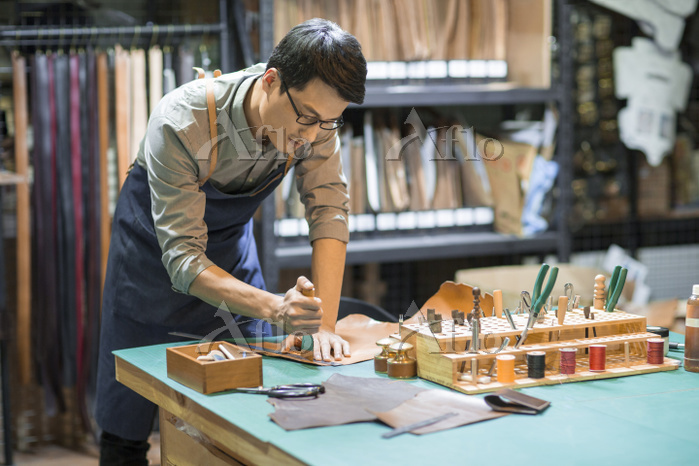 Young leather craftsman workin・・・