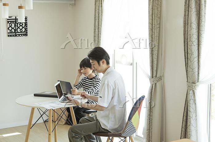 テレワークをする父親とタブレットPCを見る男の子
