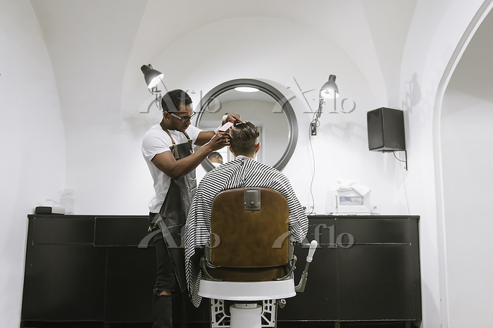 Barber cutting hair of a custo・・・