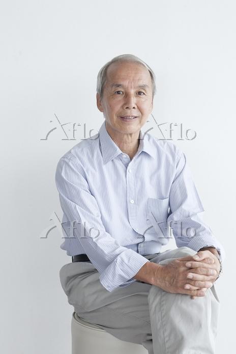 足を組んで座るシニアの日本人男性