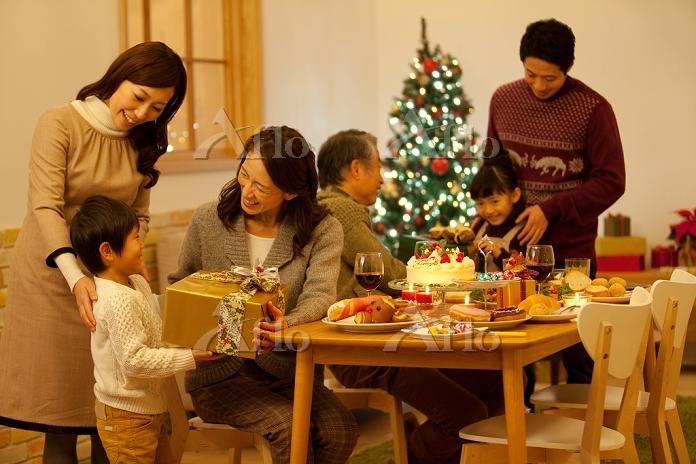 クリスマスプレゼントを渡す3世代家族