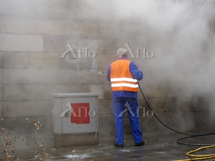 Worker removing graffiti with ・・・